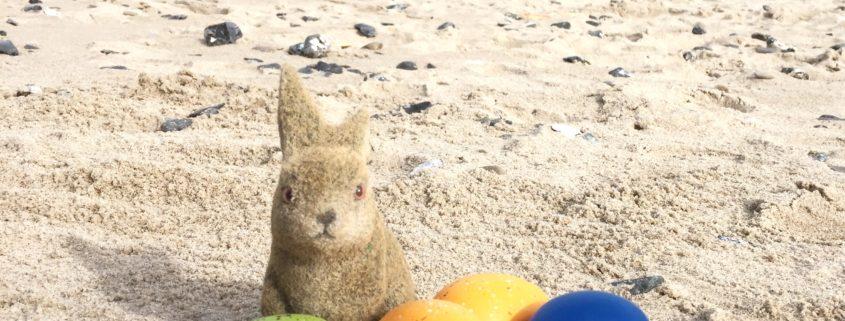 Osterhase findet Osterei am Strand